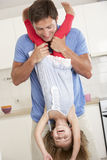 Padre Holding Daughter Upside abajo en casa Fotografía de archivo libre de regalías