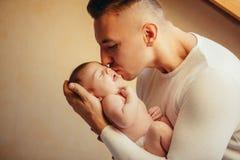 Padre Holding Newborn Baby en casa cerca de la ventana Fotografía de archivo libre de regalías