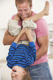 Padre Holding Son Upside abajo en casa Fotografía de archivo libre de regalías