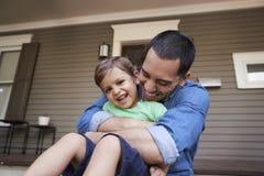 Padre Hugging Son As ellos Sit On Porch Of House junto fotografía de archivo
