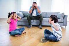 Padre infastidito che si siede sul sofà mentre combattimento dei bambini Immagini Stock