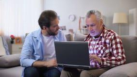 Padre invecchiato di spiegazione del giovane figlio come utilizzare computer portatile, tecnologie moderne, dispositivo stock footage