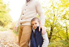 Padre irreconocible con su hijo en bosque del otoño Foto de archivo