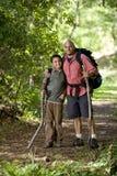 Padre ispanico e figlio che fanno un'escursione sulla traccia in legno Immagine Stock Libera da Diritti