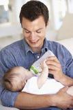 Padre joven With Baby Feeding en Sofa At Home Fotografía de archivo