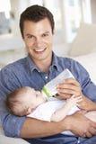 Padre joven With Baby Feeding en Sofa At Home Foto de archivo libre de regalías
