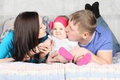 Padre joven, bebé hermoso del beso de la madre en cama Imagen de archivo