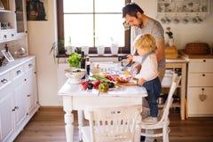 Padre joven con cocinar del niño pequeño fotos de archivo libres de regalías