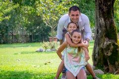 Padre joven con dos hijas en un parque en verano imagen de archivo