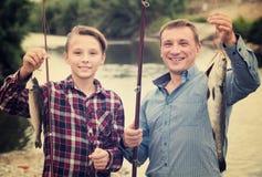 Padre joven con el hijo que mira pescados en el gancho Fotos de archivo libres de regalías