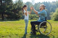 Padre joven con hija de la debilitación de la movilidad la alta-fiving imagenes de archivo