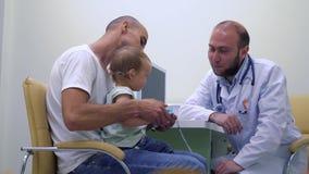 Padre joven con la pequeña hija en la consulta del pediatra metrajes