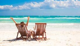 Padre joven con la pequeña hija en sillas de playa Foto de archivo libre de regalías