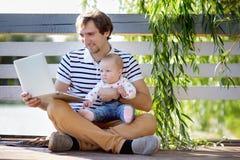 Padre joven con su bebé que trabaja en su ordenador portátil Fotos de archivo
