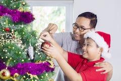 Padre joven con un niño que adorna el árbol de navidad Imagen de archivo libre de regalías