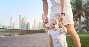 Padre joven con un ni?o y primeros pasos Padre joven con un niño en el learninig al aire libre para primeros pasos cerca de urban almacen de metraje de vídeo