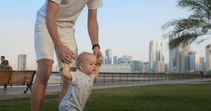 Padre joven con un ni?o y primeros pasos Padre joven con un niño en el learninig al aire libre para primeros pasos cerca de urban almacen de video