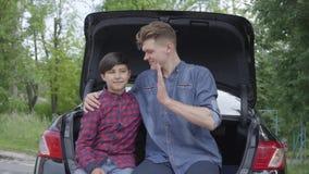 Padre joven del retrato y su hijo que se sientan en la parte de atrás del coche al aire libre El hombre que abraza al muchacho, g almacen de metraje de vídeo