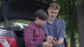 Padre joven del retrato y su hijo que se sientan en la parte de atrás del coche al aire libre El muchacho que comprueba el destor almacen de metraje de vídeo