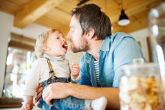 Padre joven en casa con su pequeño hijo que come la galleta junto fotos de archivo libres de regalías