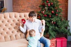 Padre joven feliz que juega con su hijo del bebé cerca del árbol de navidad Imagen de archivo