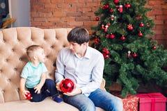 Padre joven feliz que juega con su hijo del bebé cerca del árbol de navidad Fotografía de archivo libre de regalías