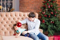 Padre joven feliz que juega con su hijo del bebé cerca del árbol de navidad Imagen de archivo libre de regalías