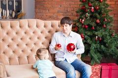 Padre joven feliz que juega con su hijo del bebé cerca del árbol de navidad Imágenes de archivo libres de regalías