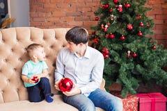 Padre joven feliz que juega con su hijo del bebé cerca del árbol de navidad Imagenes de archivo