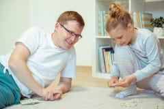 Padre joven feliz que juega con su peque?a hija linda en casa fotos de archivo