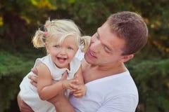Padre joven hermoso del papá de la escena de la familia que plantea jugar con su hija del bebé en tiempo feliz de la vida del pra Foto de archivo