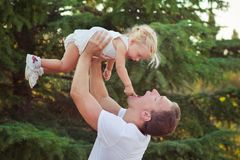 Padre joven hermoso del papá de la escena de la familia que plantea jugar con su hija del bebé en tiempo feliz de la vida del pra Foto de archivo libre de regalías
