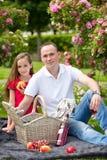 Padre joven hermoso que se sienta en una tela escocesa en un parque verde con su pequeña hija bonita con una cesta de mimbre para Imagenes de archivo