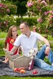 Padre joven hermoso que se sienta en una tela escocesa en un parque verde con su pequeña hija bonita con una cesta de mimbre para Foto de archivo