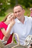 Padre joven hermoso que se sienta en una tela escocesa en un parque verde con su pequeña hija bonita con una cesta de mimbre para Imagen de archivo libre de regalías