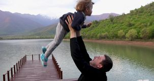Padre joven juguetónamente lanzar para arriba en aire y coger a poco hijo del niño almacen de metraje de vídeo