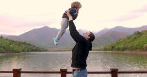 Padre joven juguet?namente lanzar para arriba en aire y coger a poco hijo del ni?o metrajes