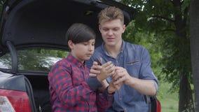 Padre joven lindo y su hijo que se sientan en la parte de atrás del coche al aire libre El muchacho que comprueba el destornillad almacen de metraje de vídeo