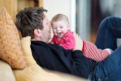 Padre joven orgulloso feliz con la hija reci?n nacida del beb?, retrato de la familia junto imagen de archivo
