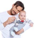 Padre joven orgulloso que presenta con su bebé Imagen de archivo libre de regalías
