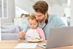Padre joven que alimenta a su bebé y que trabaja en el ordenador portátil Fotos de archivo