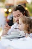Padre que alimenta a su niña Imagenes de archivo