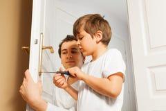 Padre joven que ayuda a su hijo a fijar el tirador de puerta fotos de archivo libres de regalías
