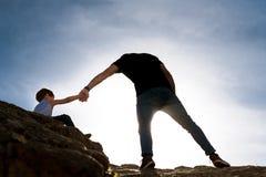 Padre joven que da la mano amiga a su hijo que sube las rocas como metáfora de los desafíos de la vida fotos de archivo