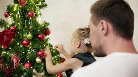 Padre joven que detiene a su pequeña hija linda en sus brazos que le ayudan a colgar una bola de oro en un árbol de navidad almacen de metraje de vídeo
