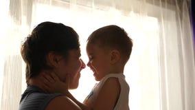 Padre joven que detiene a su pequeño niño cerca de una ventana Rayos de Sun a través de la ventana Risa y alegría del niño metrajes