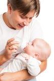 Padre joven que detiene y que alimenta a su bebé Fotografía de archivo libre de regalías