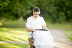 Padre joven que empuja un cochecito en parque fotos de archivo libres de regalías