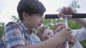 Padre joven que enseña a su hijo a fijar el primer de la vespa Vista lateral del muchacho lindo con destornillador, intentando de almacen de video