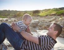 Padre joven que juega con el hijo del bebé como mintiendo en la playa, smilin Foto de archivo libre de regalías